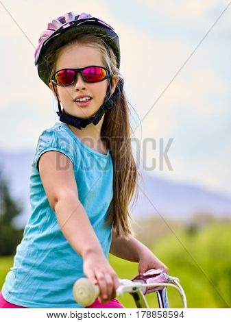 Child traveling bicycle in summer park. Girls road bike for running on green grass. Cycling trip is good for health. Portrait of little girl in rainbow goggles and helmet.