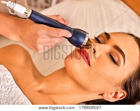 Ultrasonic facial treatment on ultrasound face machine. Woman with closed eyes has electric lift massage spa salon. Stimulation male muscles. Professional equipment microcurrent therapy in hand.