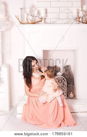 Beautiful mother sitting with her baby girl 1 year old in room. Motherhood. Childhood. 20s.