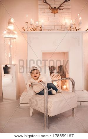 Cute baby girl sitting in retro chair in room. Wearing knitted sweater and denim pants. Looking at camera. Childhood.