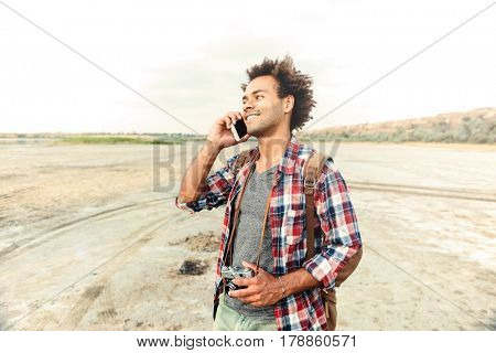 Cheerful african young man with old vintage photo camera standing and talking on cell phone