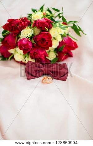 Close up of wedding bouquet of red tulips and white roses wedding rings and butterfly bouquet to match. Place for text