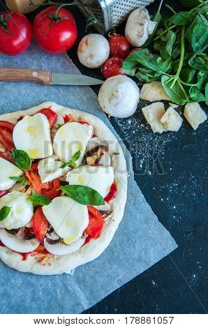 Top View Of Dough Of Pizza With Tomatoes Mushrooms And Mozarella Ready To Bake On A Parchment Paper.