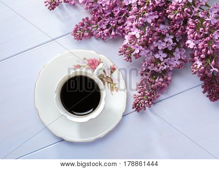 Cup of coffee and branches of blooming lilac on  wooden table.