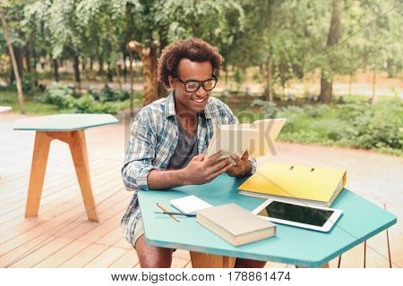Happy handsome young man in glasses reading and studying in outdoor cafe