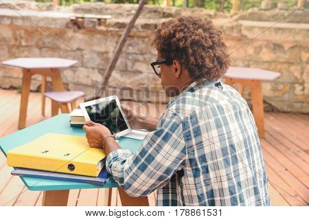 Back view of concentrated african young man sitting and using tablet at the table