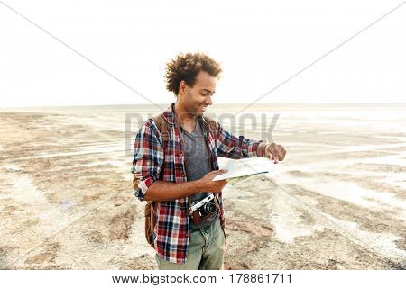 Cheerful african young man with backpack standing and examening map outdoors
