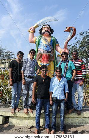 People Posing In Front Of Demon Mahishasura Statue