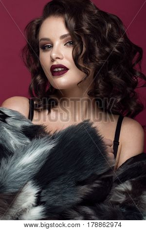 Beautiful woman with evening make-up, dark lips and long curls hair . Smoky eyes. Fashion photo. Picture taken in the studio on a red background.