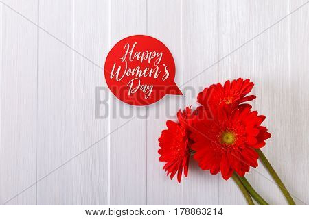 Gerbera flowers on white wood vintage background. Happy Womens day speech bubble. 8 march or Valentines day love design. Painted wooden planks.