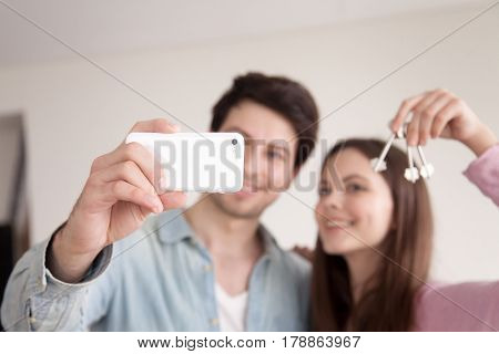 Young happy man and woman make selfie on smartphone, holding keys of new home after buying house apartment. Wife and husband purchased property, capturing moment on photo showing keys, phone in focus