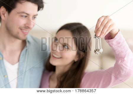 Smiling woman showing keys of apartment, looking at her husband. Young defocused couple preparing to move in their own house, real estate purchasing, successful property investment, focus on keys