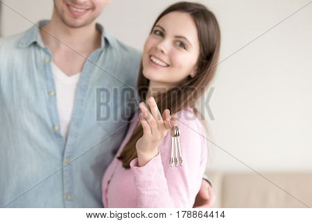 Attractive lady putting a bunch of keys on finger, showing she with her beloved man are owners of new apartment, man and woman holding their own home keys, young family proud of property purchasing