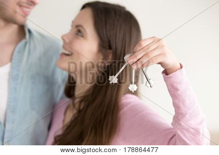 Couple successfully paid off real estate mortgage and got keys to their own flat or apartment, young wife showing house keys, looking at her husband with excitement, relocating or renting property