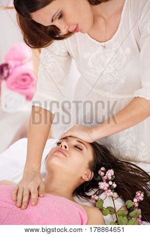 Sideview of messeur doing facial massage on young woman lying on couch with pink flowers
