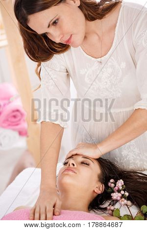 Careful messeur doing facial massage on pretty lady at bright room of modern spa salon