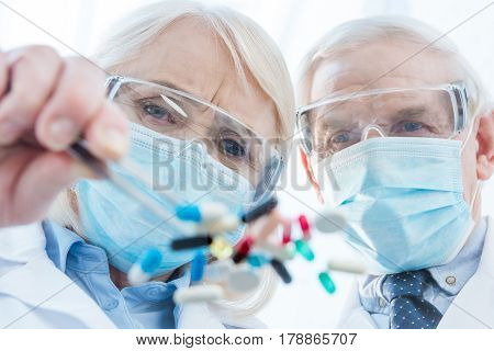 Scientists In Protective Workwear Working With Various Pills