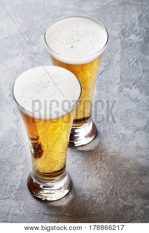 Two lager beer glasses on stone table