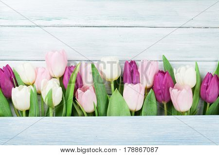 Colorful tulips over wooden background. Easter card with space for your greetings