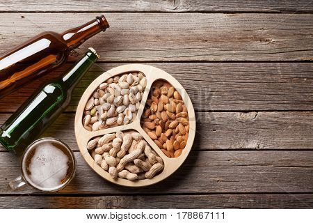 Lager beer glass, bottles and snacks on wooden table. Various nuts. Top view with copy space