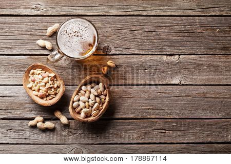 Lager beer mug and snacks on wooden table. Various nuts. Top view with copy space