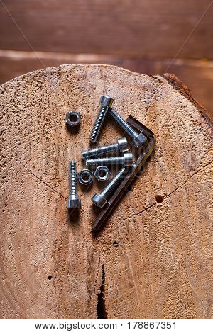 Hex head screw, nut and hexagon key on a wood background.
