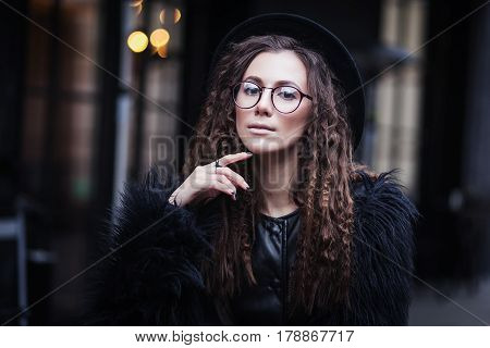 Portrait of a beautiful girl with brown eyes in glasses in a black hat and coat with fur in the cityscape looking in camera. The girl is like Harry Potter.