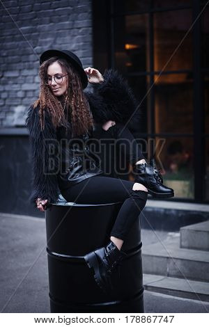 Portrait of a beautiful girl with brown eyes in glasses in a black hat and coat with fur sits on a barrel in the cityscape and looking down. The girl is like Harry Potter.