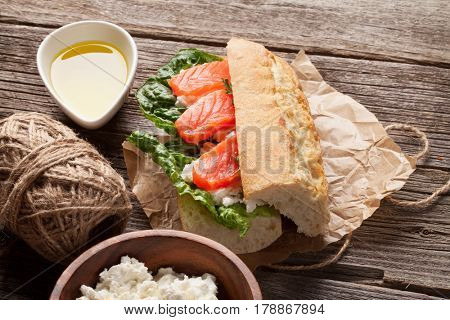 Sandwich with ciabatta bread, salmon, cheese and romaine salad on wooden table