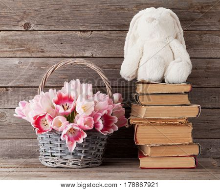 Pink tulips bouquet basket and rabbit toy in front of wooden wall. Easter greeting card