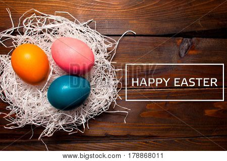 Multicolored Chicken, Dyed Eggs For The Easter Holiday In The Nest On Wooden Weathering Background W