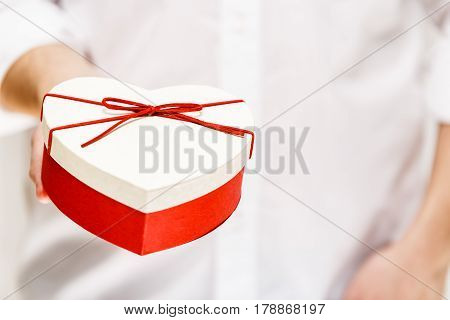 Male hand holding a heart-shaped gift box. Present wrapped with ribbon and bow. Valentines day love package. Man in white shirt.