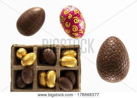 High angle view of a variety of wrapped and unwrapped Easter chocolate eggs on a white background