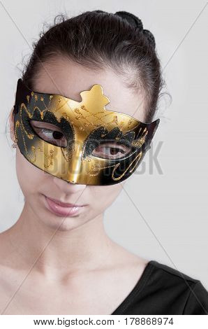 Girl Brunette In A Theatrical Mask Looks Down