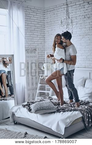 Love is in the air. Full length of beautiful young couple bonding and smiling while standing on the bed