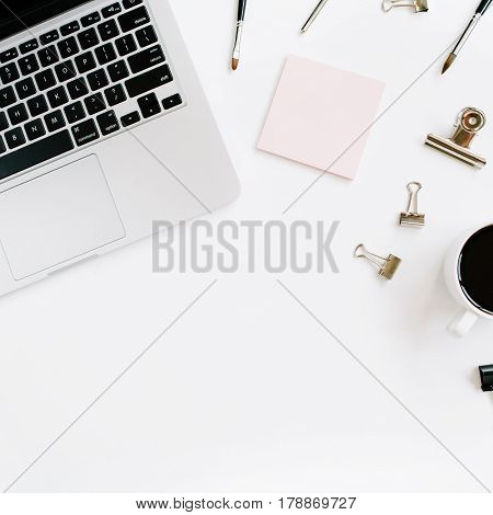 Pale pink stylish home office workspace desk with laptop coffee and office stuff on white background. Flat lay top view. Entrepreneur office concept.