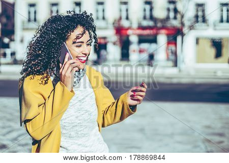 Beautiful laughing Brazilian curly woman standing on street and talking by phone with friend smiling hipster brunette lady using smartphone for call her sister with copy space for your text message