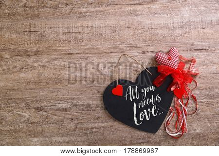 All you need is love design. Black and red hearts with rope and bow on wood rustic background. Concept for romantic love. Wooden grunge board.