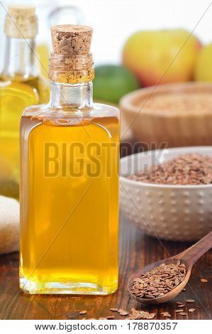 Brown flax seeds on spoon and nonrefined flaxseed oil in glass bottle on wooden table. Vertical shot