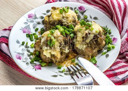 meat stack (meat rissoles with fried onions boiled egg potatoes and cheese) cooked in the oven lay on plate