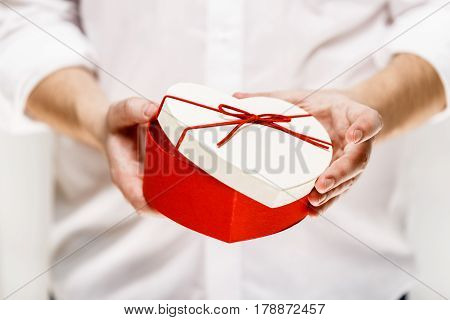 Male hands holding a heart-shaped gift box. Opened present wrapped with ribbon and bow. Valentines day love package. Man in white shirt.