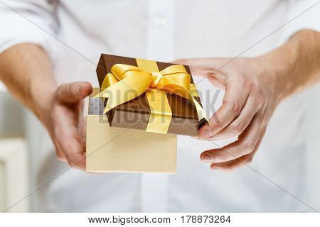 Male hands holding a gift box. Opened present wrapped with ribbon and bow. Christmas or birthday package. Man in white shirt.