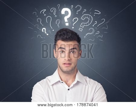 Young casual businessman with white question marks above his head