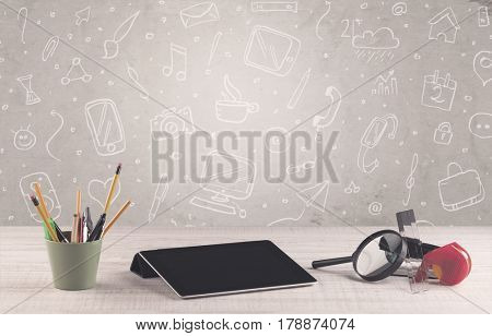 Close up of business office desk with laptop tablet in front of brown wall background full of drawn communication icons and school items concept