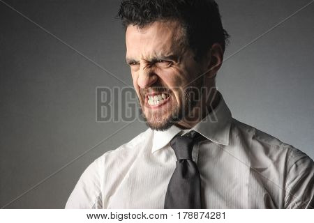 Angry businessman grinding his teeth