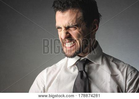Angry businessman grinding his teeth