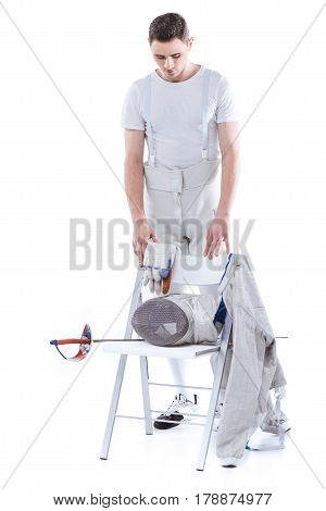 Young Man Professional Fencer Looking At Fencing Equipment On Chair
