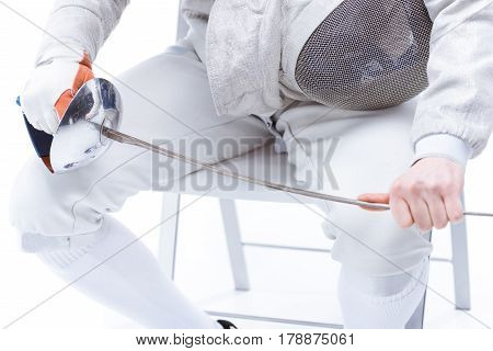 Cropped Shot Of Professional Fencer Holding Helmet And Rapier While Sitting On Chair