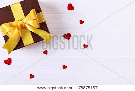 Gift box with red satin hearts. Present wrapped with ribbon and bow. Christmas or birthday package. On white wooden table.