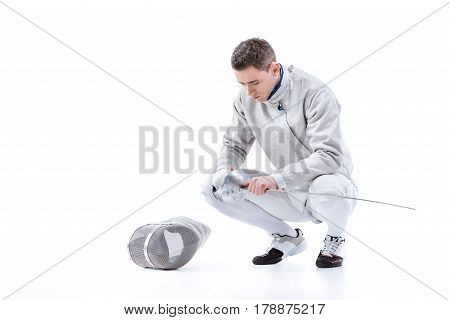Young Man Professional Fencer Holding Sword And Crouching On White